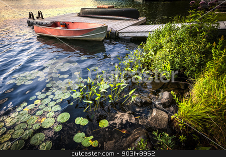 Rowboat at lake shore at dusk stock photo, Rowboat tied to dock on beautiful lake at rocky shore with aquatic plants. Ontario, Canada. by Elena Elisseeva