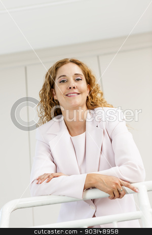 Happy businesswoman standing in hallway stock photo, Smiling proud business woman standing in office hallway leaning on railing shot from below by Elena Elisseeva