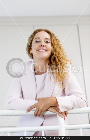 Portrait of happy businesswoman in office stock photo, Smiling proud business woman standing in office hallway leaning on railing shot from below by Elena Elisseeva