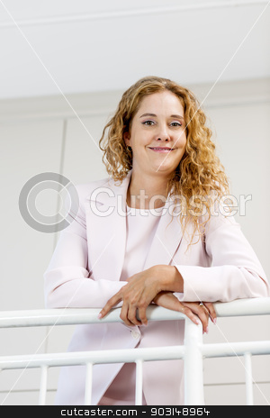 Portrait of confident businesswoman in office stock photo, Confident successful business woman standing in office hallway leaning on railing and smiling by Elena Elisseeva