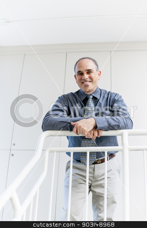 Businessman standing in office hallway smiling stock photo, Portrait of happy proud business man standing in office hallway leaning on railing by Elena Elisseeva