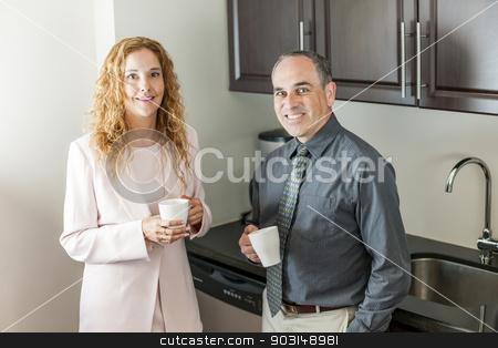 Coworkers on coffee break stock photo, Two office coworkers on coffee break standing in kitchen by Elena Elisseeva