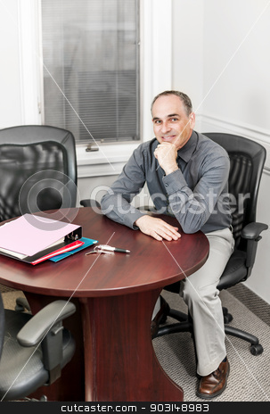 Businessman sitting in office meeting room stock photo, Middle aged business man looking happy sitting at table in office meeting room by Elena Elisseeva