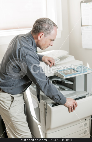 Man opening photocopier in office stock photo, Business man opening photocopy machine in office by Elena Elisseeva
