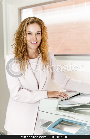Businesswoman using photocopier in office stock photo, Smiling business woman operating photocopy machine in office by Elena Elisseeva