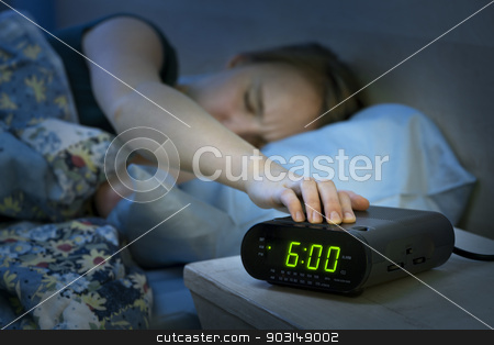 Woman waking up early with alarm clock stock photo, Young woman pressing snooze button on early morning digital alarm clock radio by Elena Elisseeva