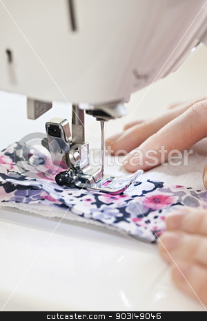 Hands with sewing machine stock photo, Closeup of hands guiding fabric through sewing machine needle and thread by Elena Elisseeva