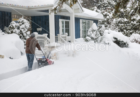 Man using snowblower in deep snow stock photo, Man using snowblower to clear deep snow on driveway near residential house after heavy snowfall by Elena Elisseeva