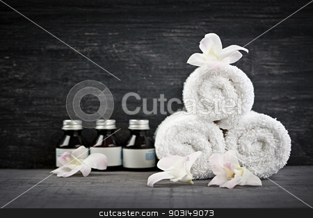 Rolled up towels and products at spa stock photo, White rolled up towels with body care products at spa by Elena Elisseeva
