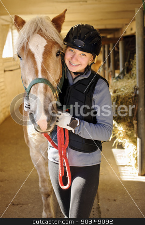 Rider with horse in stable stock photo, Young female rider with horse inside stable by Elena Elisseeva