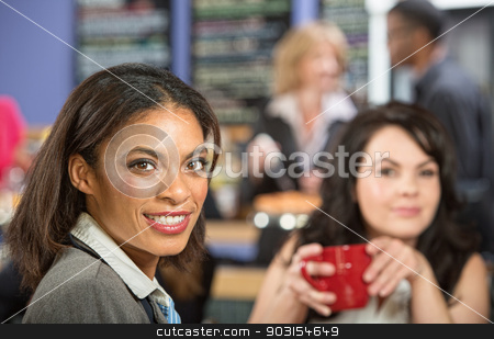 Two Businesswomen in Cafe stock photo, Two happy businesswomen with coffee mug in cafe by Scott Griessel