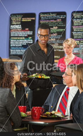 Man Serving Customers in Cafe stock photo, Young barista serving diverse group of customers by Scott Griessel