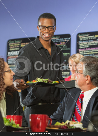 Barista Bringing Food stock photo, Handsome coffee house barista serving group of executives by Scott Griessel