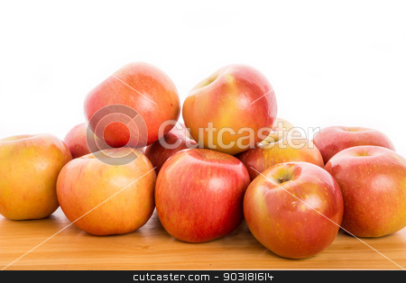 Bunch of Apples on Wood Table with White Background stock photo, A bunch of fuji apples on a wood table with a white background by Darryl Brooks