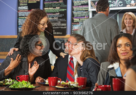 Laughing Group of Business People stock photo, Four businesspeople laughing together during lunch in cafe by Scott Griessel