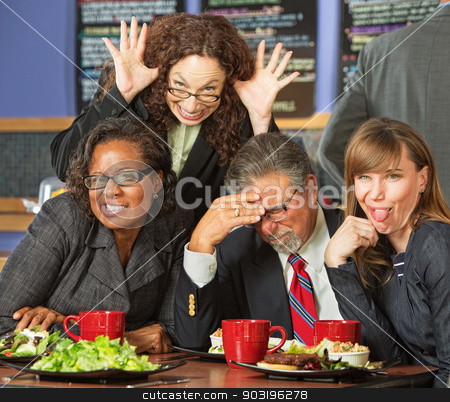 Business People in Awkward Pose stock photo, Embarrassed man with coworkers making faces in cafe by Scott Griessel