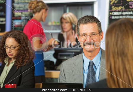 Businessman Sitting in Cafe stock photo, Handsome cheerful businessman talking sitting in cafeteria by Scott Griessel