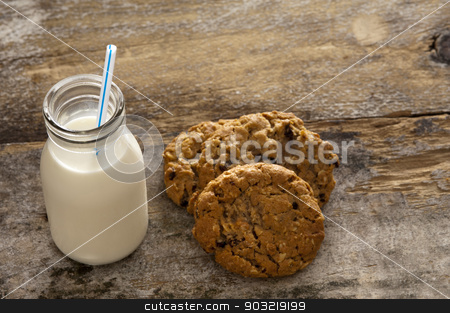 Milk and cookies childhood treat stock photo, Milk and cookies childhood treat set out on an old rustic wooden table with a glass bottle of fresh milk with a straw and a pile of crunchy cookies, high angle with copyspace by Stephen Gibson