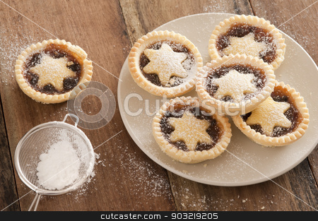 Delicious Christmas mince pies with stars stock photo, Preparing a plate of delicious Christmas mince pies decorated with pastry stars and sprinkling them with icing sugar from a sieve in a country kitchen on a wooden counter, high angle view by Stephen Gibson