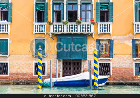 Blue Boat by Blue and Yellow Poles stock photo, Colorful gondola posts in a Venice canal by Darryl Brooks