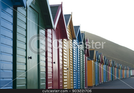 Row of colorful wooden beach huts stock photo, Row of colorful wooden beach huts overlooking Whitby Sands in North Yorkshire looking along the front facades of the receding line of huts by Stephen Gibson