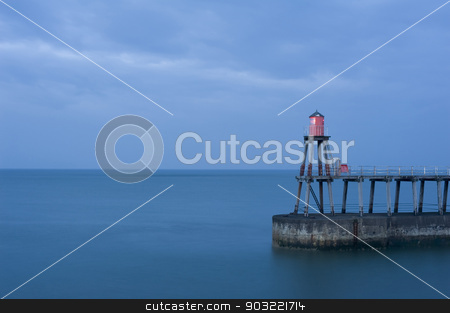 Whitby pier stock photo, Whitby pier with one of the navigation beacons to guide shipping into the harbour at night on a calm ocean with copyspace by Stephen Gibson