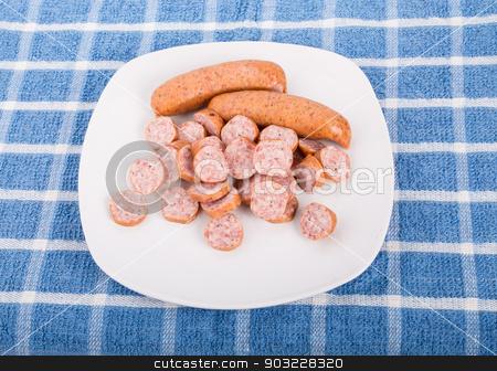 While and Sliced Kielbasa on a Plate stock photo, Sliced and whole kielbasa sausage on a white plate and blue towel by Darryl Brooks