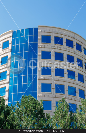 Round Stone Building with Blue Windows stock photo, Blue Windows in curved building reflecting sky and clouds by Darryl Brooks