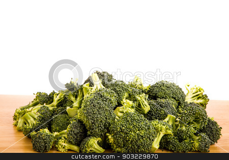 Fresh Green Broccoli on Wood Table stock photo, Fresh broccoli on a wood table with a white background by Darryl Brooks