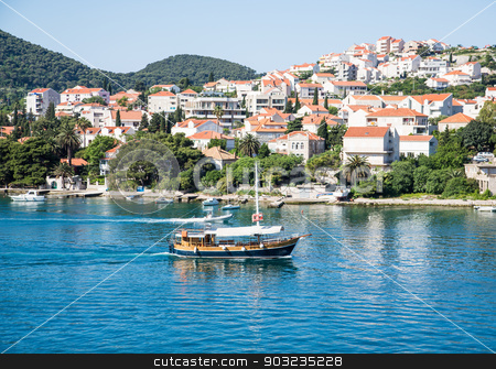 Empty Wood Boat in Blue Bay of Croatia stock photo, Beautiful port in Croatia with white yachts on calm blue water by Darryl Brooks