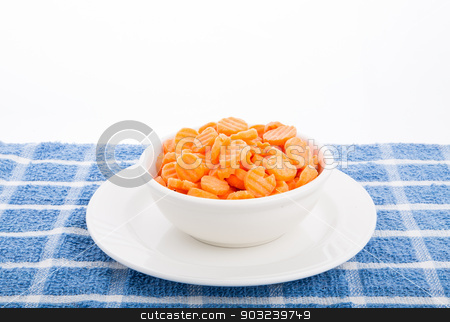 Sliced Carrots in White Bowl stock photo, Crinkle cut sliced carrots in a white bowl on white plate and blue towel by Darryl Brooks
