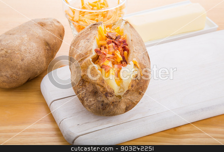 Baked Potatoes with Bacon and Cheese stock photo, A baked potato loaded with cheese and bacon on a wood board with a stick of butter in the background by Darryl Brooks