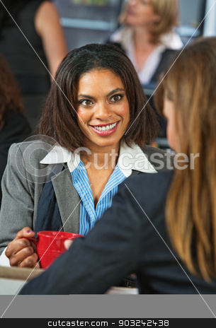 Smiling Woman with Mug stock photo, Smiling coworker listening to friend during coffee break by Scott Griessel