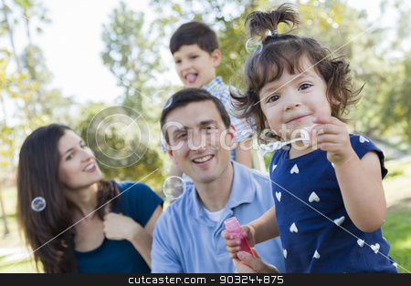 Cute Young Baby Girl Blowing Bubbles with Family in Park stock photo, Cute Young Baby Girl Blowing Bubbles with Her Family in the Park. by Andy Dean