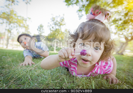 Cute Baby Girl and Brother with Lollipops in Park stock photo, Cute Baby Girl and Brother with Lollipops in the Park. by Andy Dean