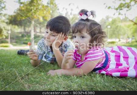 Young Brother and Baby Sister Enjoying Their Lollipops Outdoors stock photo, Cute Young Brother and Baby Sister Enjoying Their Lollipops Outdoors on the Grass. by Andy Dean