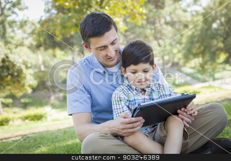 Handsome Mixed Race Father and Son Playing on Computer Tablet stock photo, Handsome Mixed Race Father and Son Playing on a Computer Tablet Outside. by Andy Dean