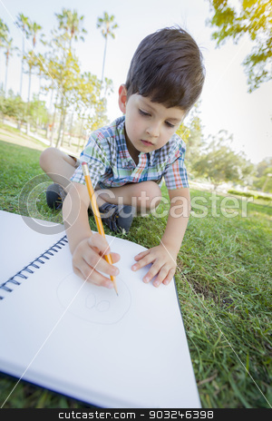Cute Young Boy Drawing Outdoors on the Grass stock photo, Cute Young Artistic Boy Drawing with Pencil and Paper Outdoors on the Grass by Andy Dean