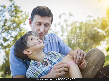 Loving Father Puts Bandage on Knee of Young Son stock photo, Loving Father Puts a Bandage on the Knee of His Young Son in the Park. by Andy Dean