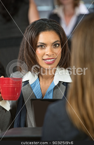 Woman Holding Coffee Cup stock photo, Smiling woman holding red coffee cup in cafe by Scott Griessel