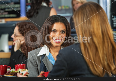 Smiling Business Woman stock photo, Smiling Black woman with coworker in cafeteria by Scott Griessel
