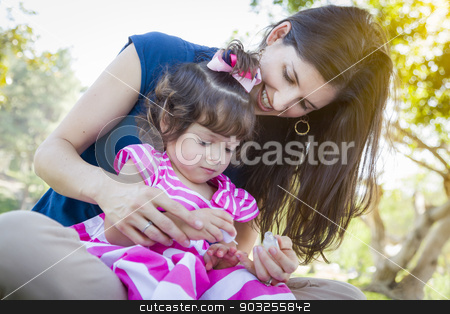 Young Mother and Cute Baby Girl Applying Fingernail Polish stock photo, Mixed Race Young Mother and Cute Baby Girl Applying Fingernail Polish in the Park. by Andy Dean