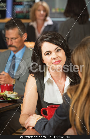 Friend Touching Woman's Hand stock photo, Grinning woman consoled by friend in cafeteria by Scott Griessel