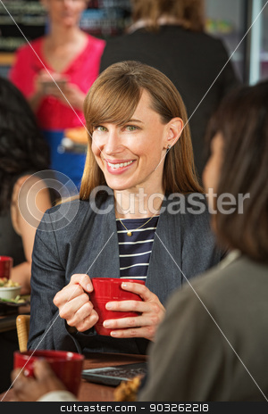 Cheerful Woman in Cafe stock photo, Cheerful business woman with red mug and friend in cafe by Scott Griessel