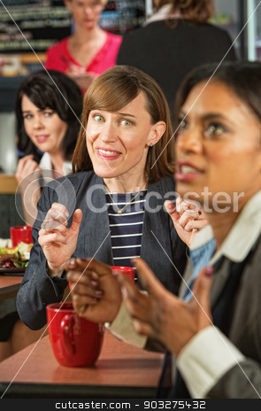 Lady Mocking Coworker stock photo, Business woman mocking coworker at table in cafeteria by Scott Griessel