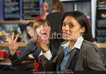 Jealous Coworker stock photo, Business woman in cafe with person making fun of her by Scott Griessel