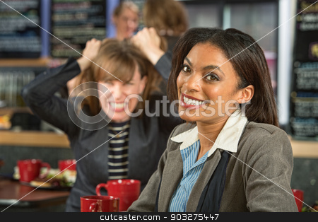 Woman with Frustrated Friend stock photo, Smiling woman in coffee house with frustrated friend by Scott Griessel