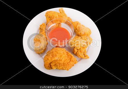 Fried Chicken with Pepper Sauce on White Plate stock photo, Fried chicken on a white plate and black background with red hot pepper sauce by Darryl Brooks