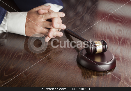 Judge Rests Hands Behind Gavel with American Flag Table Reflecti stock photo, Male Judge Rests Folded Hands Behind Gavel with American Flag Reflection on Wooden Table. by Andy Dean