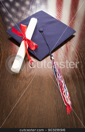 Graduation Cap and Diploma on Table with American Flag Reflection stock photo, Graduation Cap with Tassel and Diploma Wresting on Wooden Table with American Flag Reflection. by Andy Dean